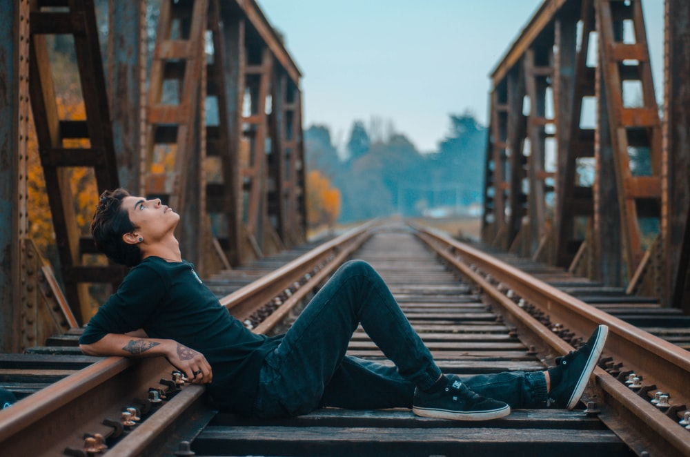 man sitting on railway looking up during daytime
