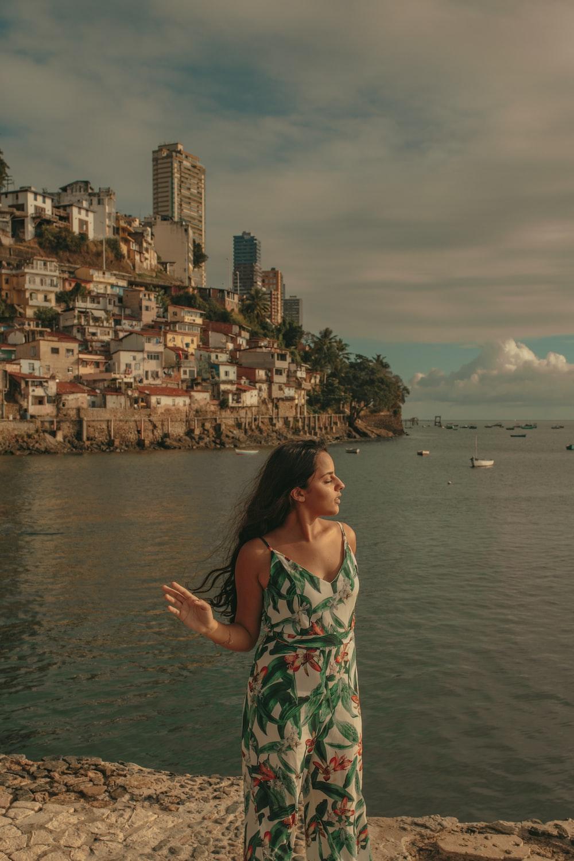 woman standing on rock beside water