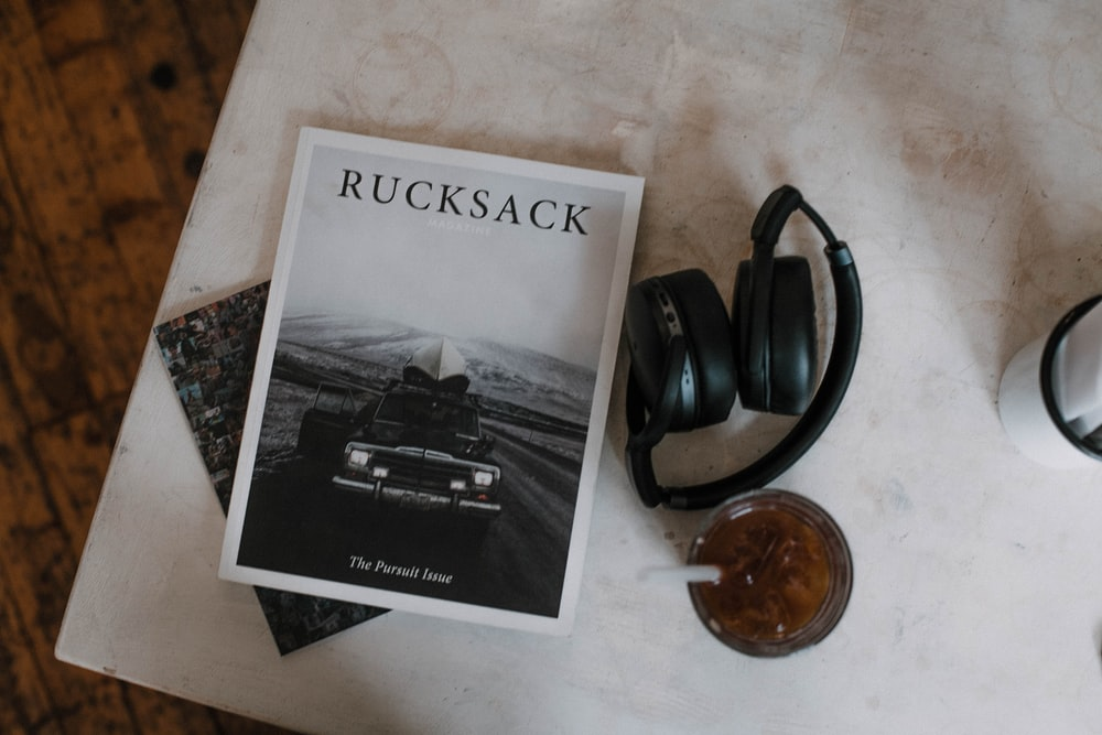 Rucksack book beside black folding headphones