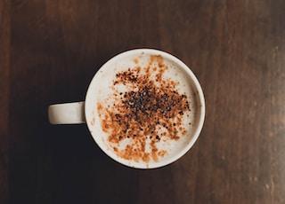 white ceramic mug on brown surface