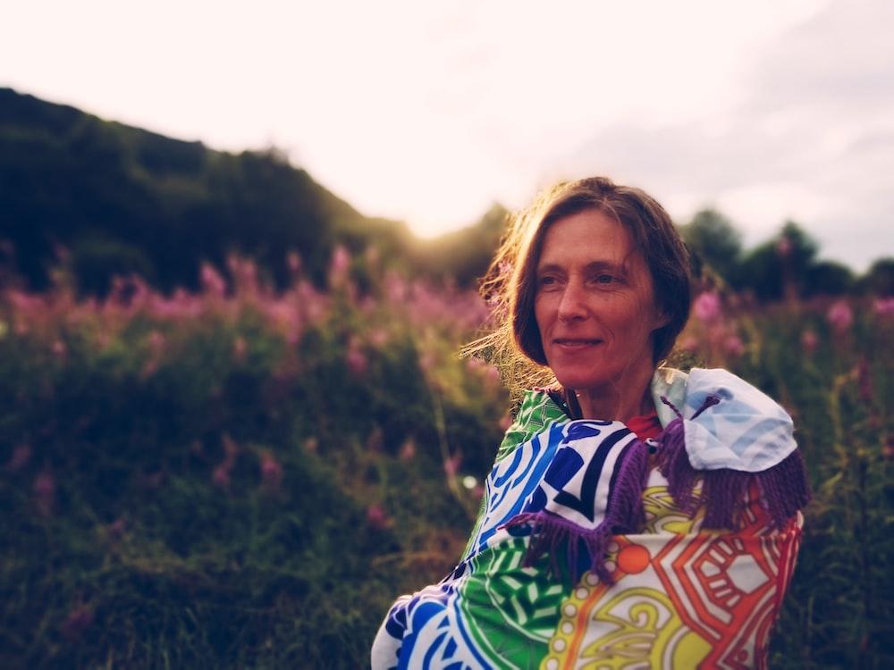 woman in multicolored jacket on flower field
