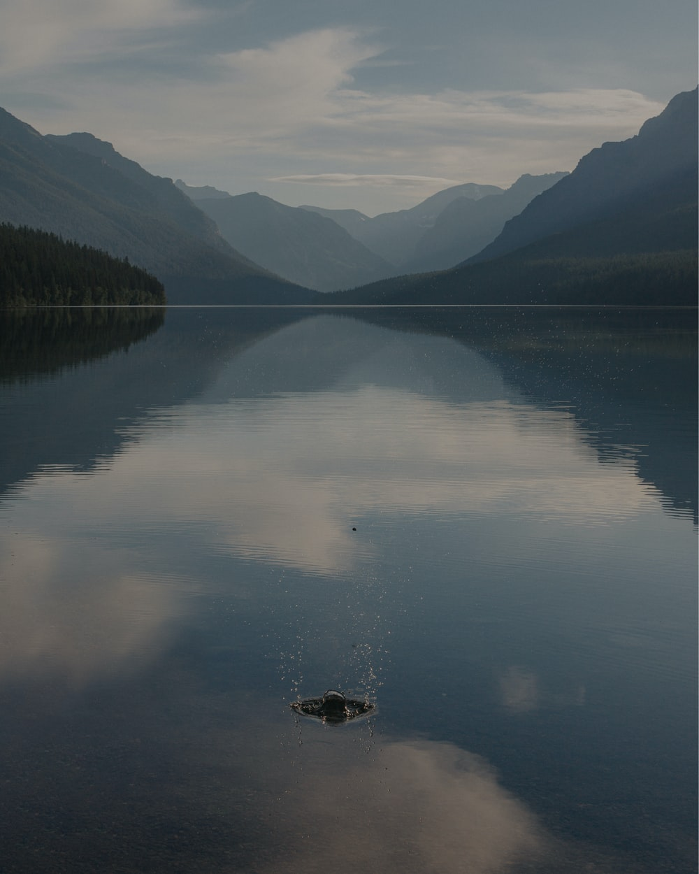 body of water near mountains during daytime