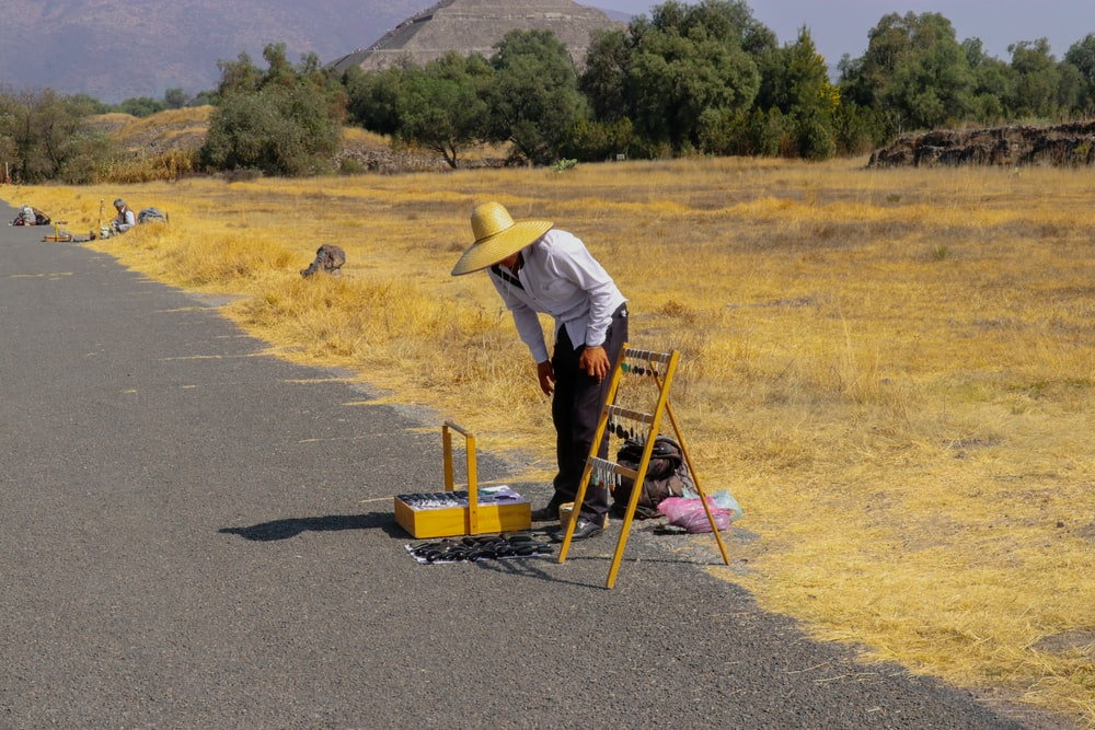 man standing near equipment on side of road