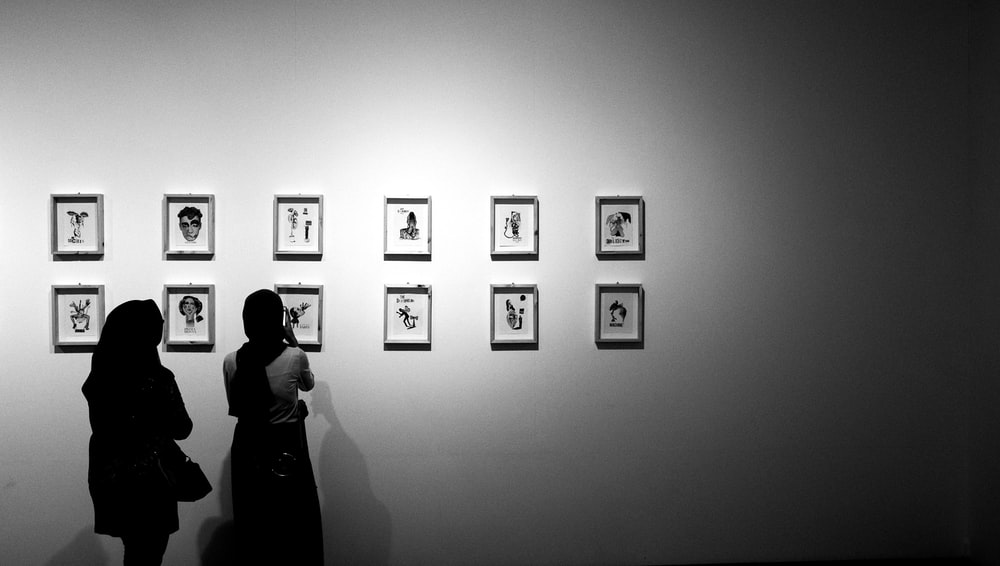 grayscale photo of 2 women standing in front of picture frames on wall