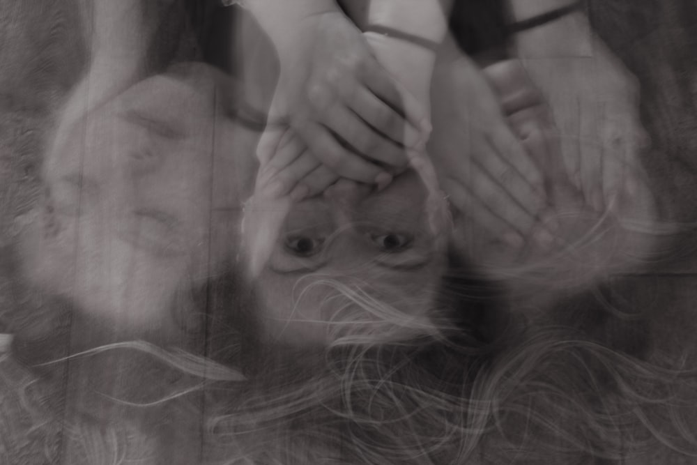 grayscale forced perspective photography of woman's face