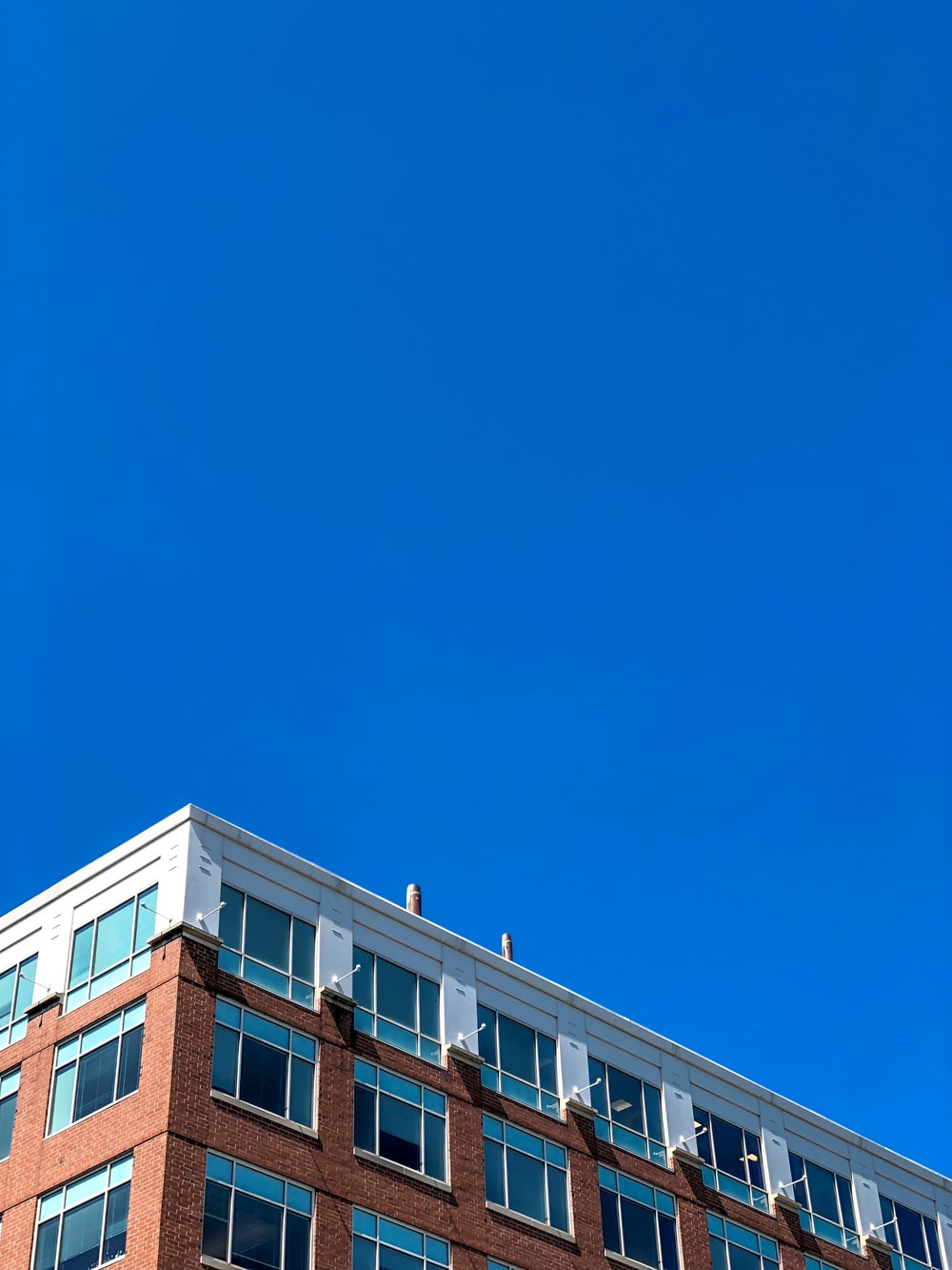 white and brown building under clear blue sky
