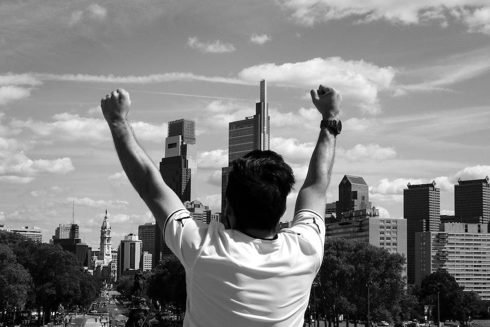 man raising both arms