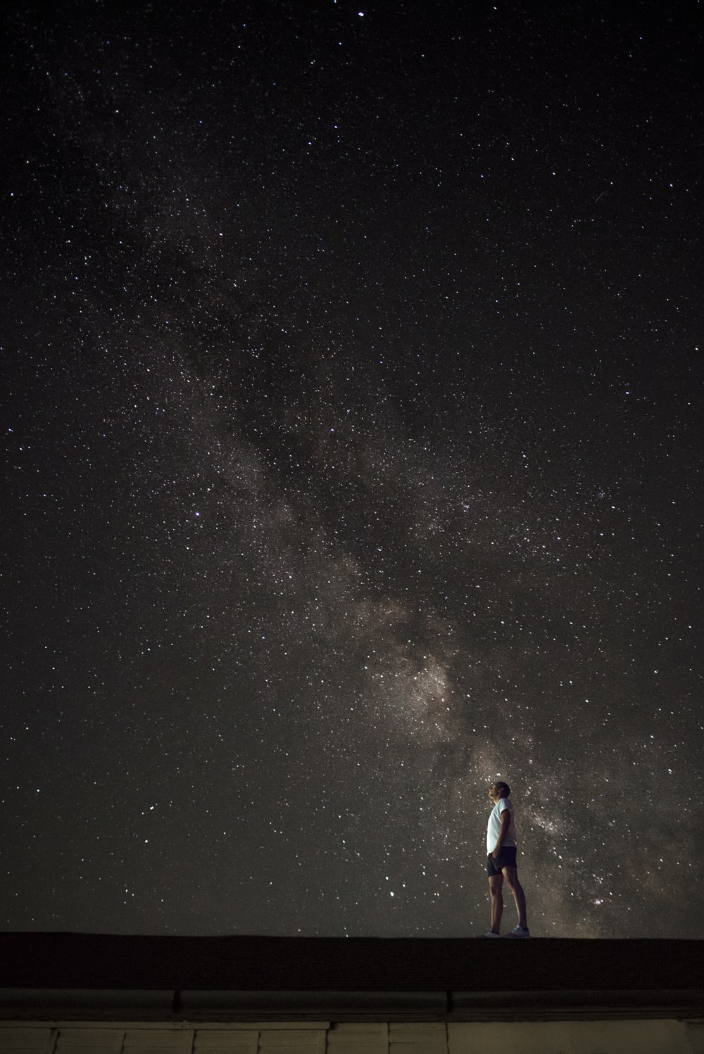 man looking up to Milky Way galaxy at night sky