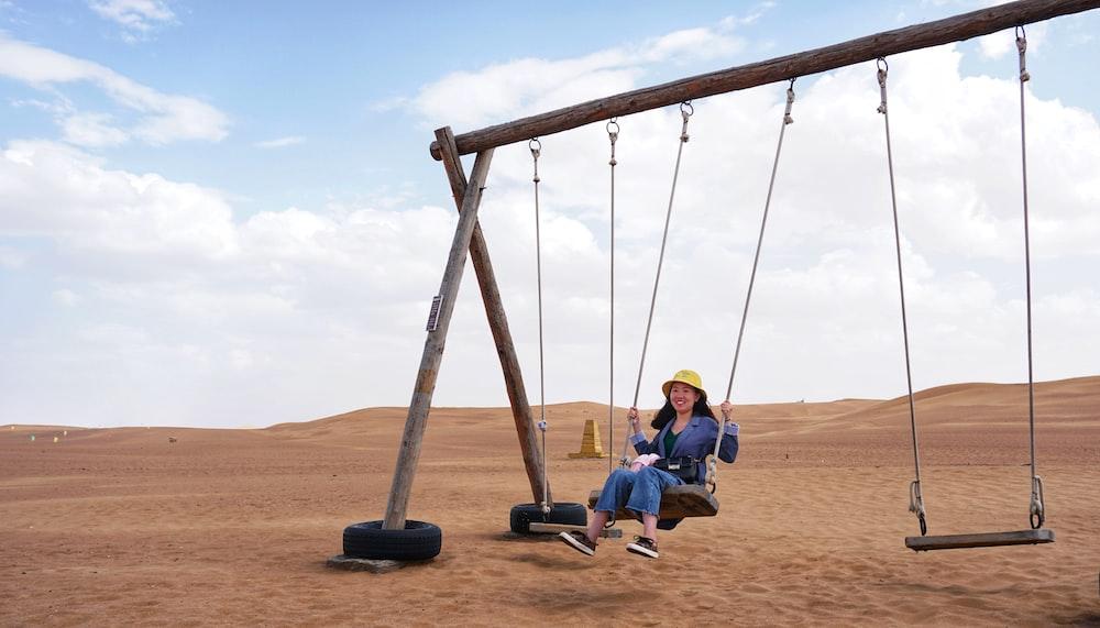 woman sitting on swing in desert