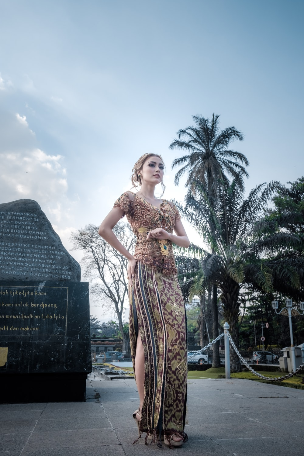 woman in multicolored floral short-sleeved maxi dress standing in front of memorial statue