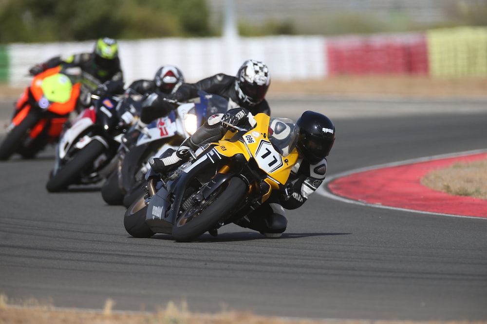 four person riding on sports bikes close-up photography