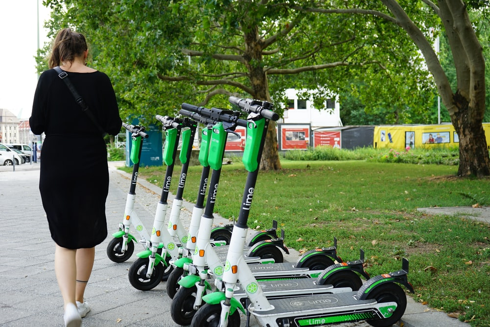 woman walking beside parked electric scooters