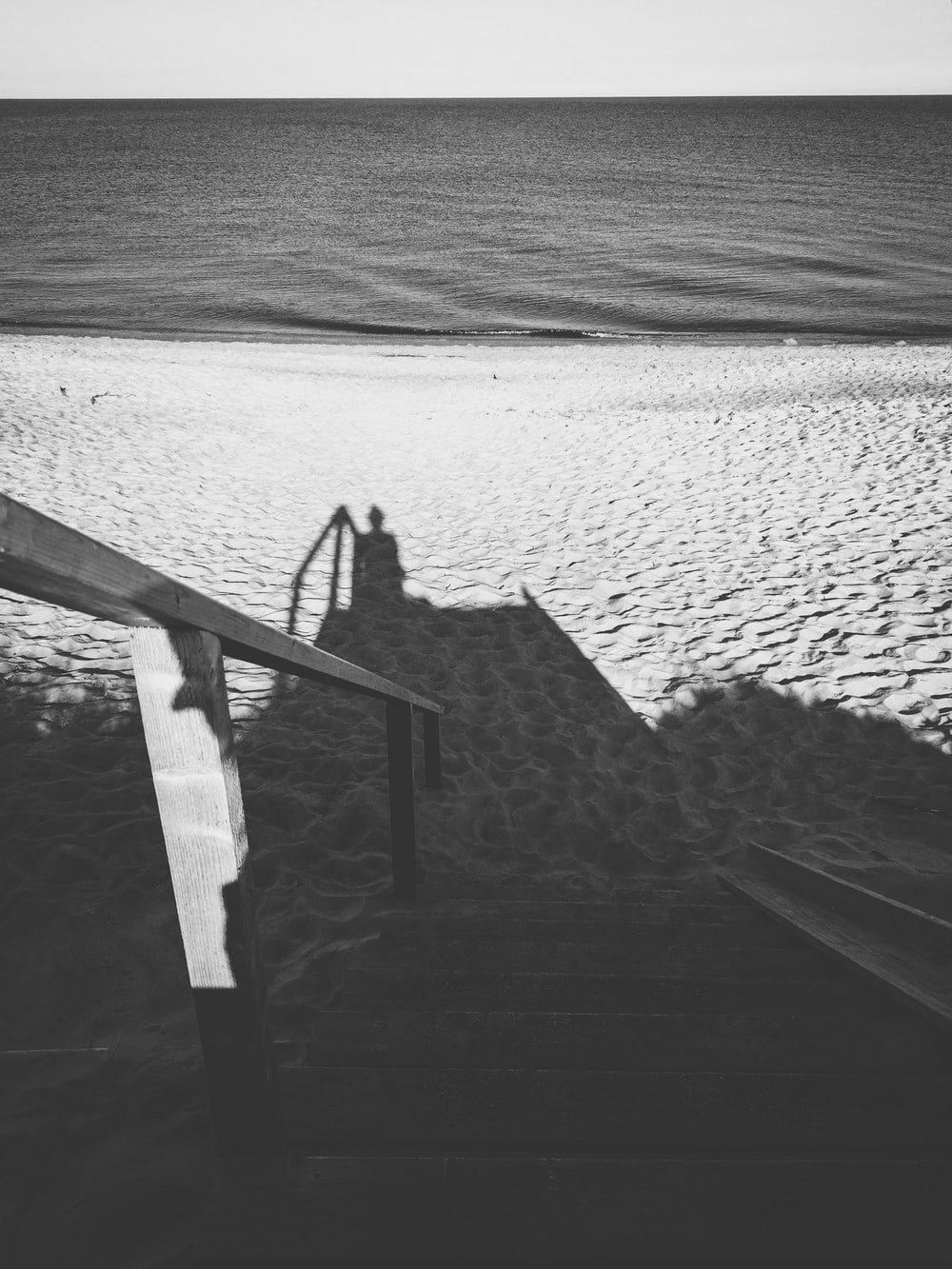 shadow of man near handrail on sand
