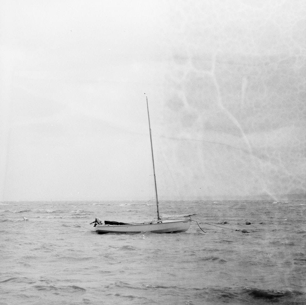 grayscale photo of sailboat anchored in beach