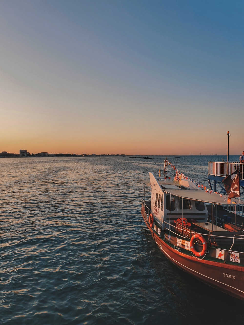 red and white boat on body of water at golden hour