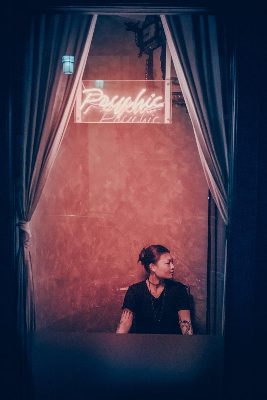 woman in black top sitting beside wall