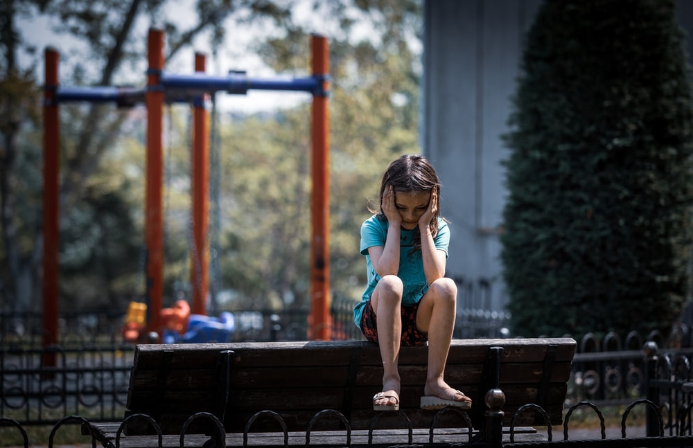 girl sitting in a bench during daytime