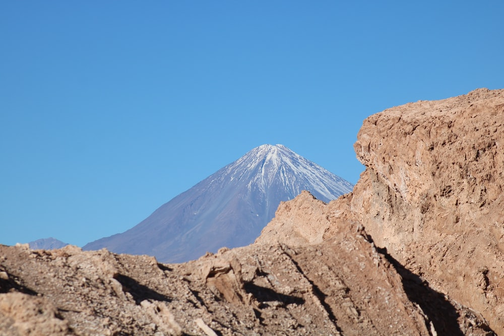 rock formation near mountain under blue sky during daytime