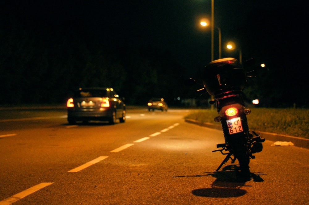 motorcycle parked besides concrete road during nighttime