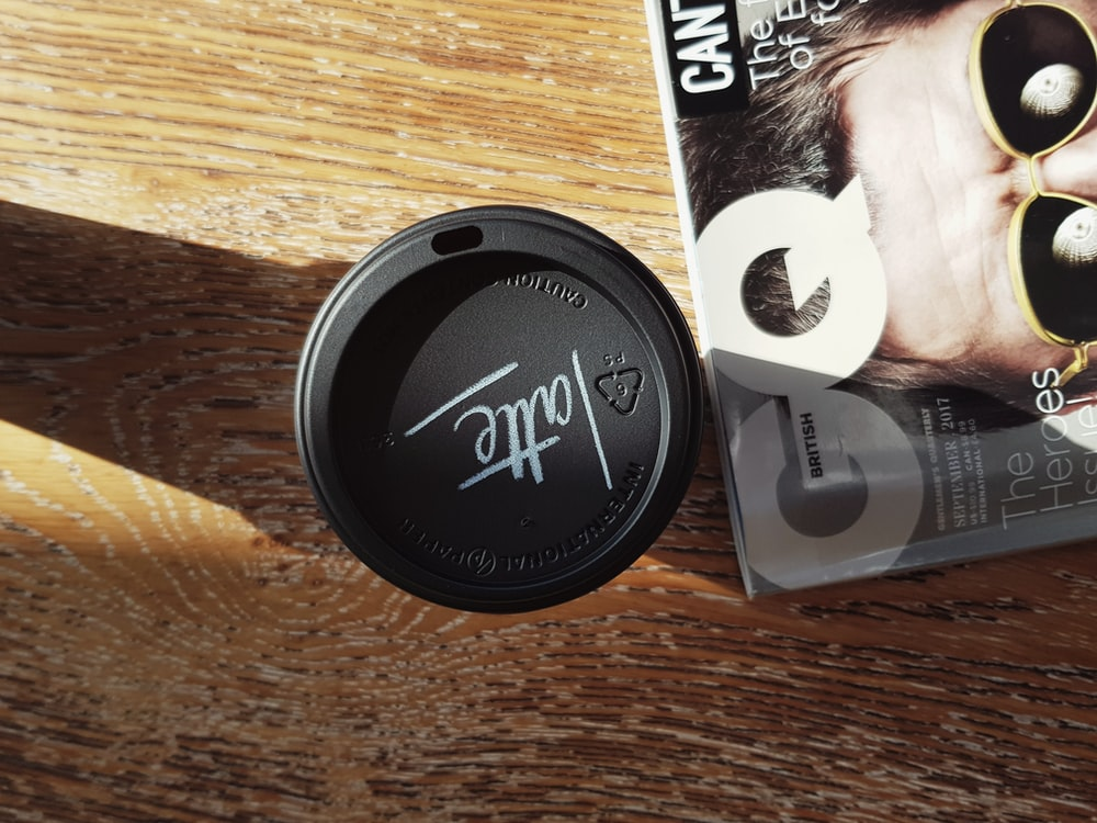 black disposable coffee cup besides GQ magazine