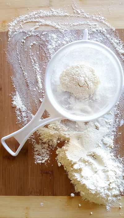 まな板の上の小麦粉と容器に入った小麦粉の画像