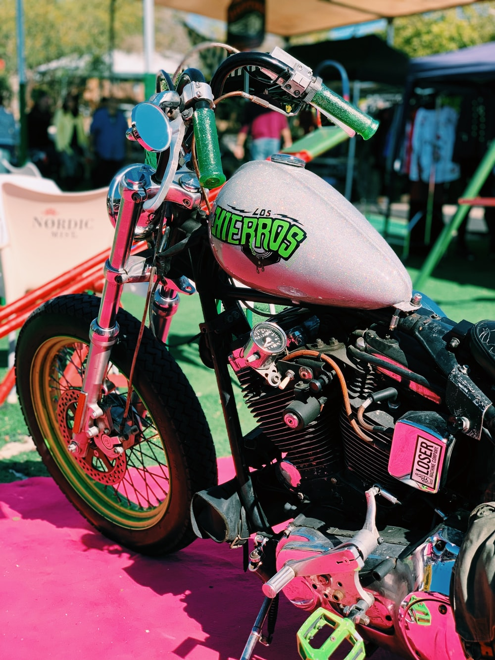 pink motorcycle parked near canopy tent