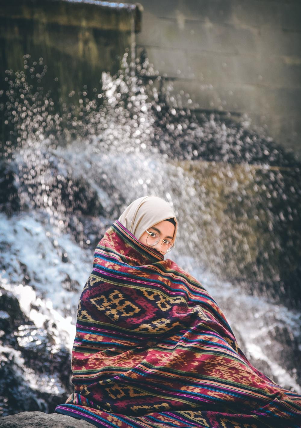 woman sitting on rock near flowing body of water