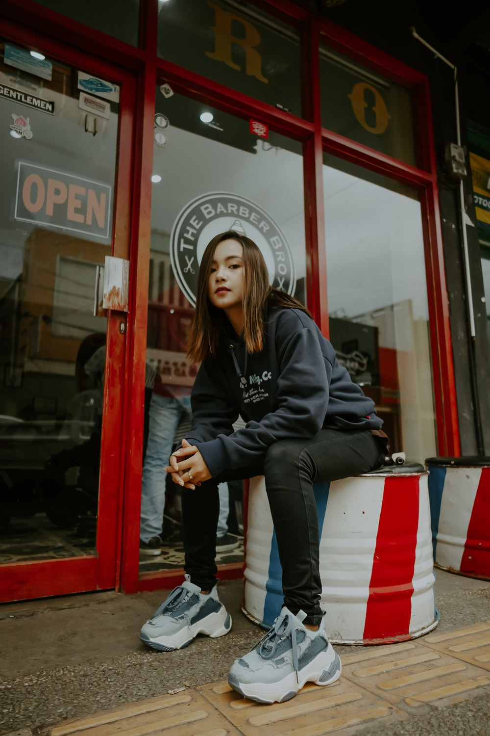 woman sitting in front of store door