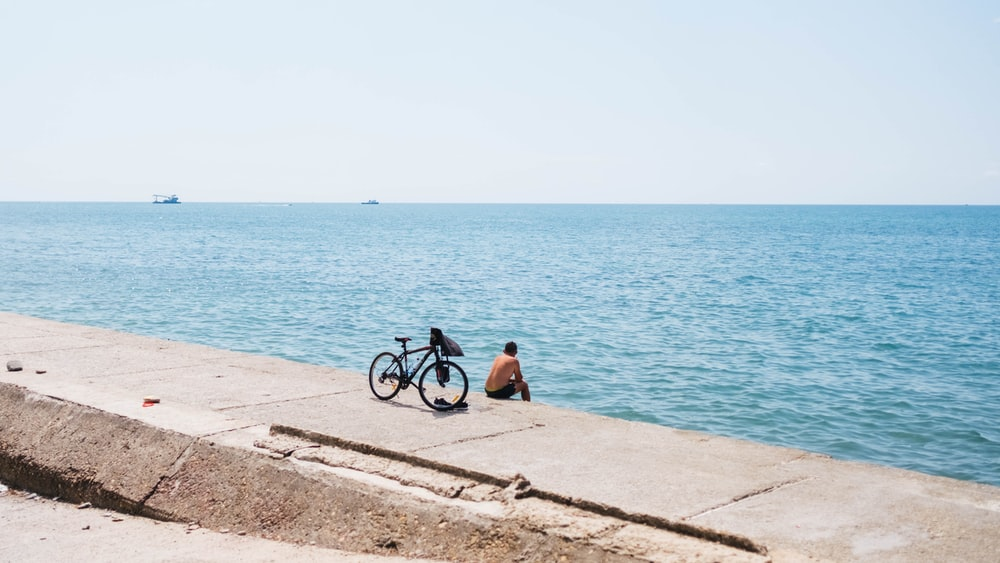man sitting beside bicycle while sitting on sea wall