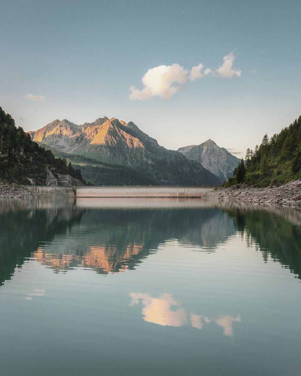 body of water near mountain under white clouds and blue sky during daytime