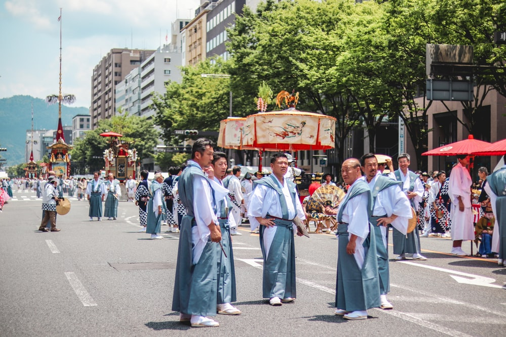 men wearing traditional dress standing on road