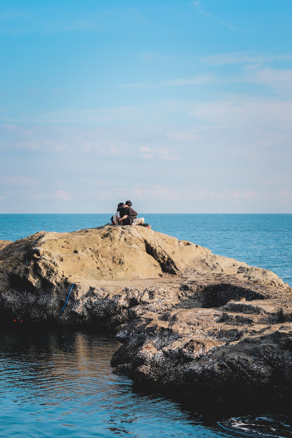 man sitting on stone beside sea under clear blue sky