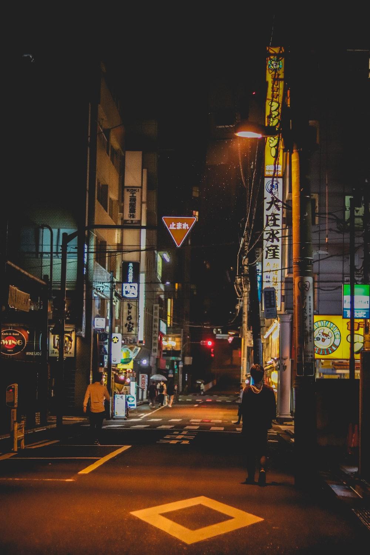 man walking on road between building at nighttime