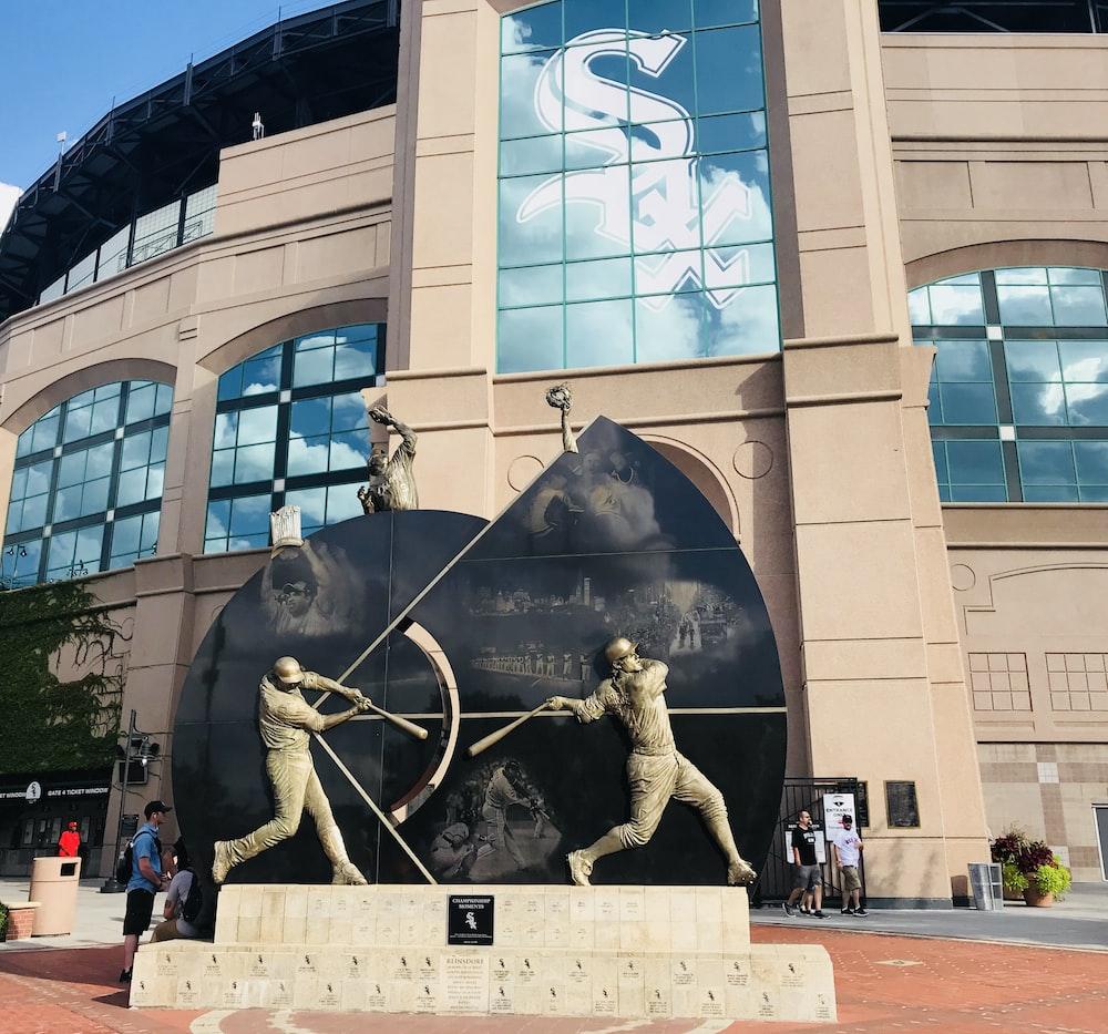 grey baseball statue near concrete building