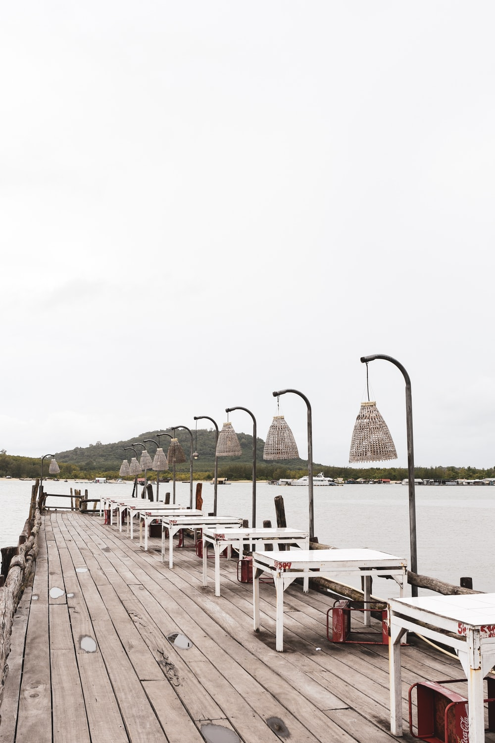 dock with tables and lampposts during day