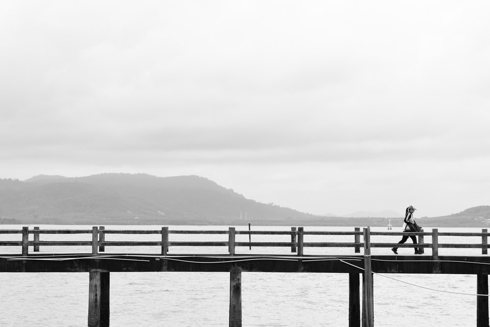 woman walking on sea dock