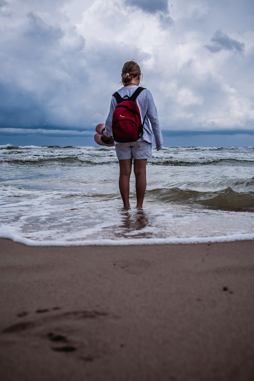 woman in gray jacket standing on seashore