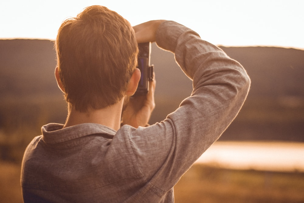 man taking pictures with DSLR camera