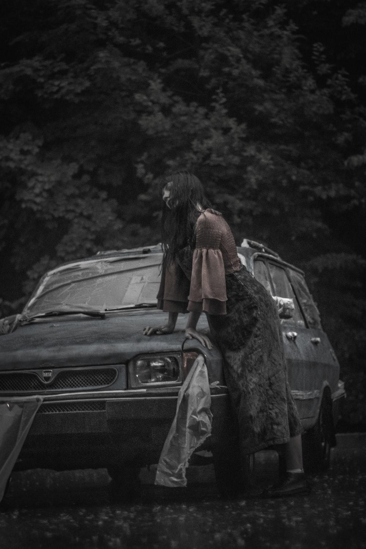 greyscale photography of woman beside vehicle