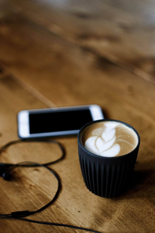 black ceramic mug with coffee lathe