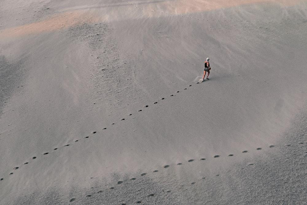 woman walking in grey sand leaving footprints
