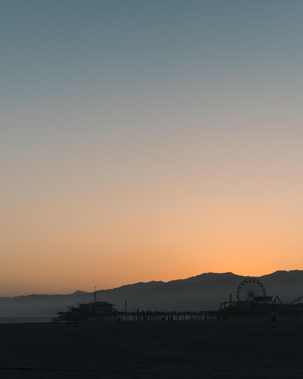 silhouette of Ferris wheel near mountains