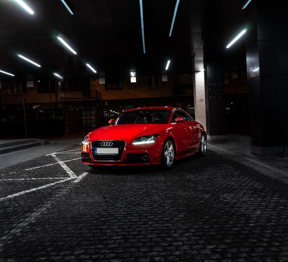 red Audi coupe parked near post