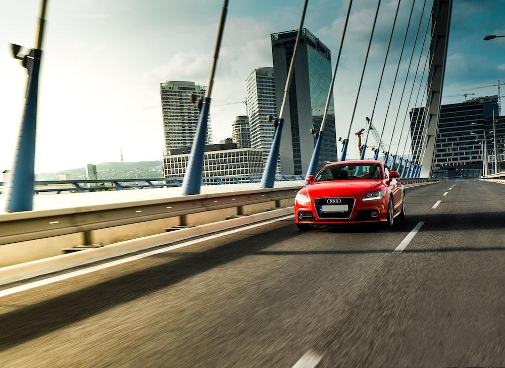 red Audi sedan running on bridge