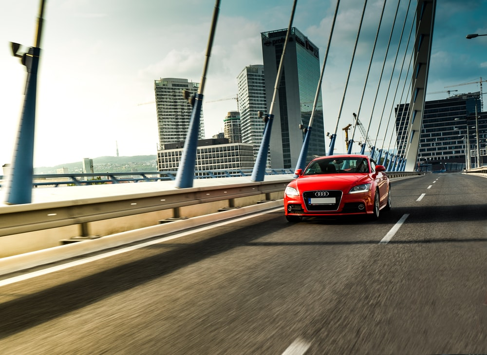 red Audi sedan running on bridge