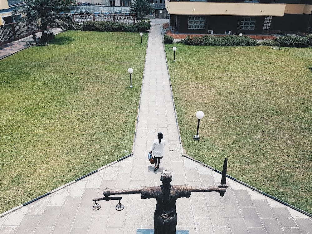 woman walking near lady justice statue