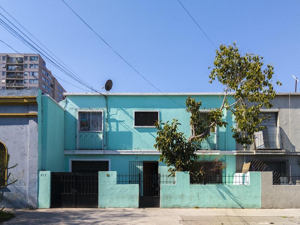teal concrete house under blue sky