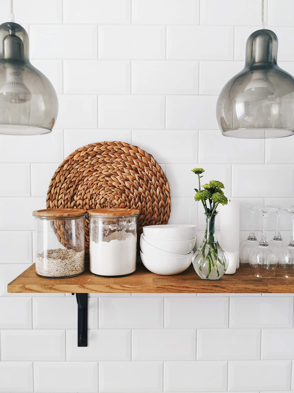 two clear glass jars on brown wooden floating shelf