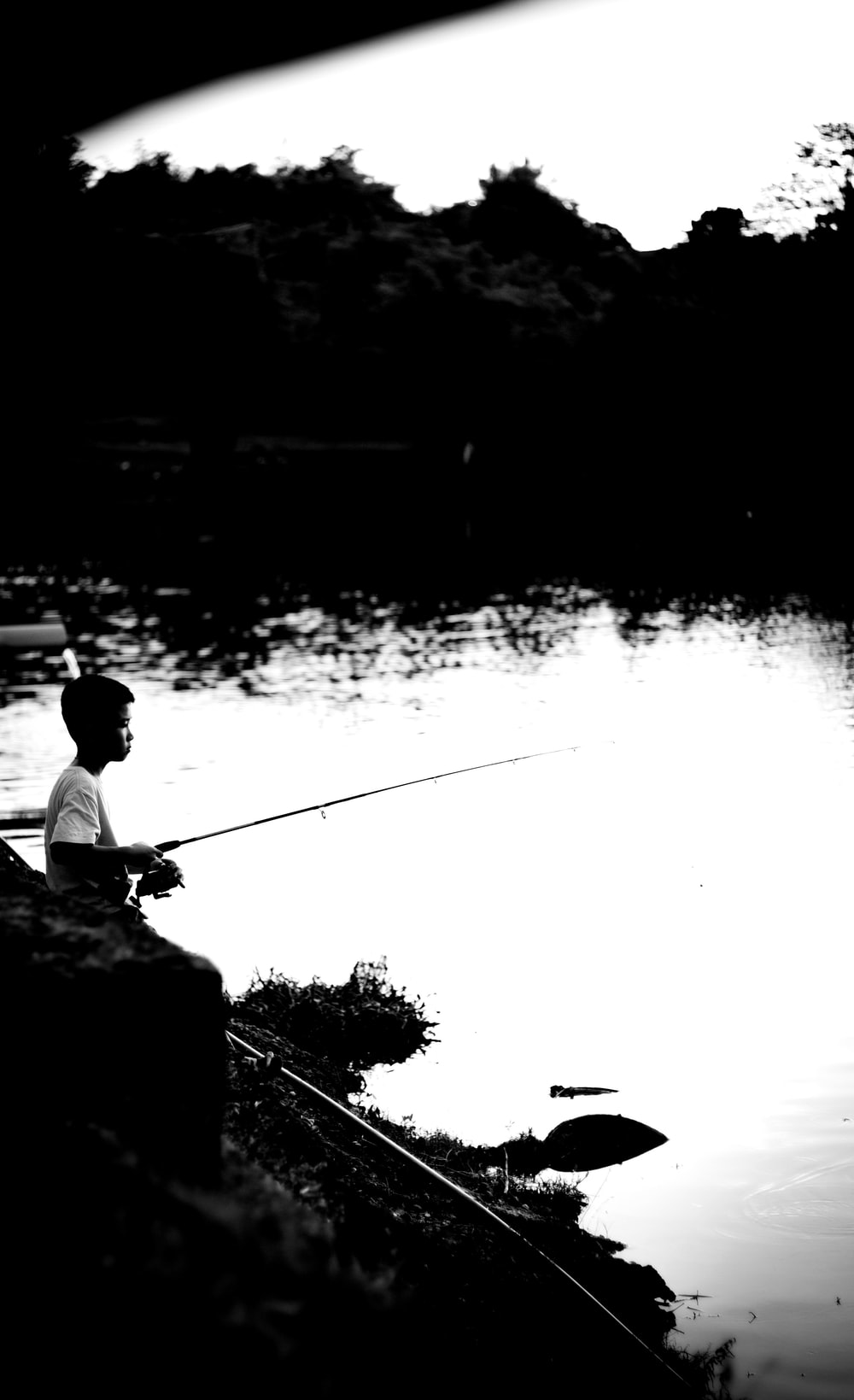 grayscale photography of boy fishing on lake