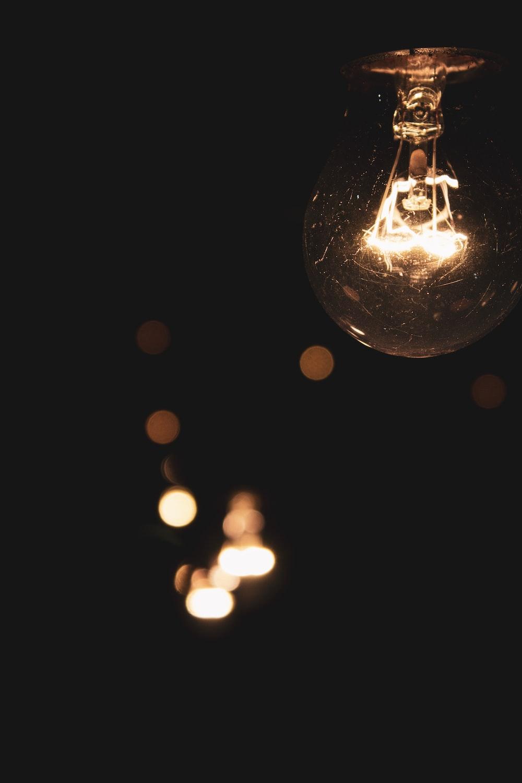 turned-on brown light bulbs on black room